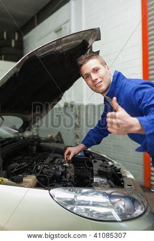 Retrato de auto mecánico gesticular pulgar hacia arriba como comprueba el nivel de aceite del coche