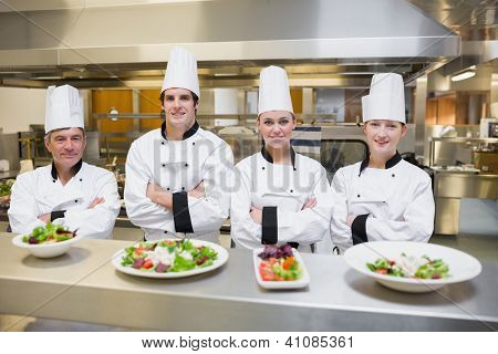 Smiling Chef's standing behind salads in the kithcen