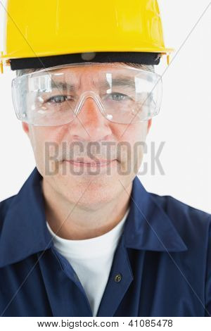 Close-up portrait of confident technician in protective glasses and hardhat over white background