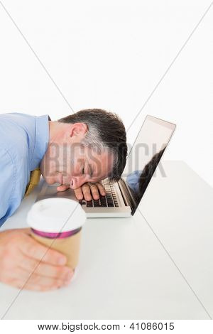 Tired man holding coffee and sleeping on his laptop on his desk in a white background