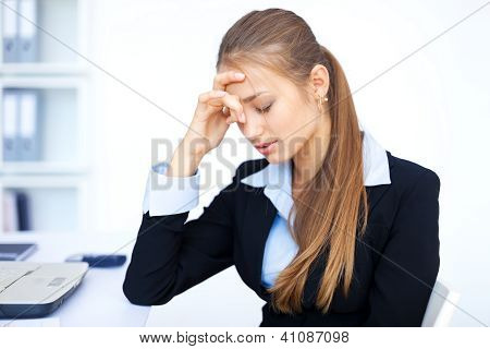 Portrait Of Tired Young Business Woman With Laptop Computer At The Office