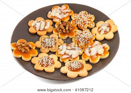 Plate With Homemade Butter Cookies With Caramel, Walnut, Almond And Sesame, White Background