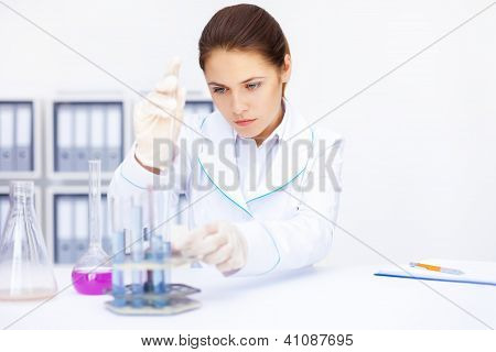 Young Chemical Female Researcher With Vials And Flasks Makes Some Experiments In Laboratory