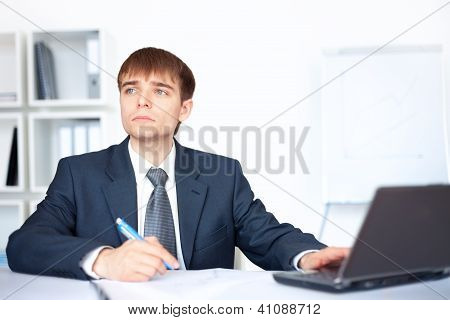 Portrait Of Young Smiling Business Man Writing On Paperwork In Office