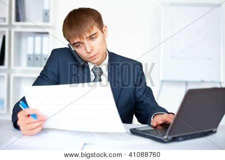 Young Businessman Talking On Mobile Phone And Reads On Paperwork In Office