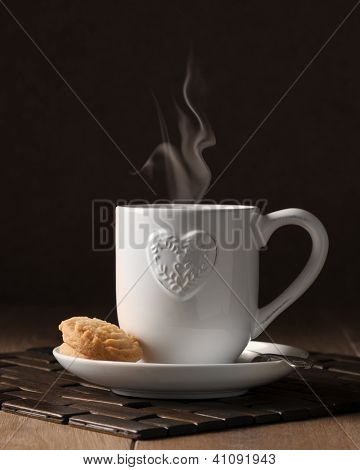 Cup of steaming coffee with biscuits on wooden table