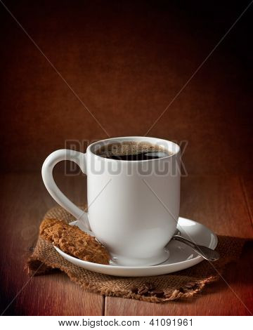 Cup of coffee with biscuits on burlap mat