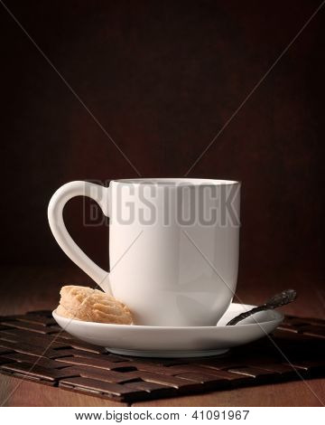 Coffee cup and saucer with biscuits on wooden table