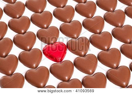 Rows of chocolate hearts with one odd one still in it's red foil wrapper, white background.