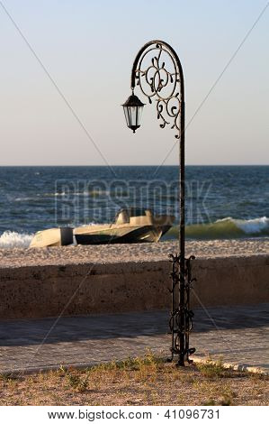 Forged Park Street Lantern  On The Beach With A Boat And A Pinnace On A Summer Morning