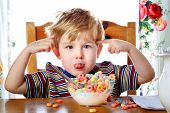stock photo of carbohydrate  - Boy misbehaving while eating breakfast cereal - JPG