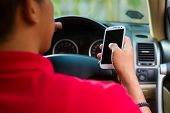 pic of steers  - Asian man sitting in car with mobile phone in hand texting while driving - JPG