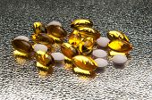 Closeup of vitamin E and vitamin D capsules on metallic background