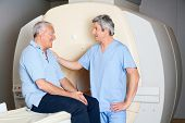 Mature male radiologic technician comforting senior patient before MRI scan