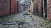 stock photo of derelict  - looking down a inner city cobblestoned alley way - JPG