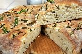 picture of flat-bread  - Homemade Italian rosemary Focaccia bread with a wedge cut out - JPG