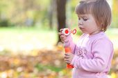 pic of leaf-blower  - beautiful little girl making bubble blower on the autumn forest - JPG