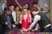 image of roulette table  - People cheering at roulette table in casino - JPG
