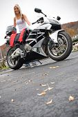 pic of crotch-rocket  - A pretty blonde woman posing with her motorcycle and riding gear - JPG