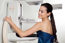 foto of mammogram  - Young female smiling while taking a mammogram x - JPG