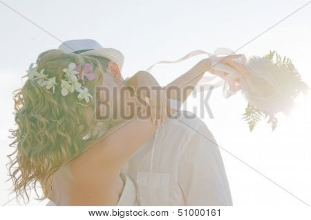 young pretty kissing wedding couple against sky