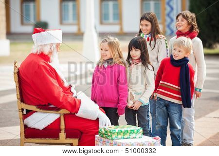 Side view of Santa Claus looking at children standing in a queue at courtyard