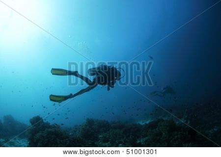 Scuba diver finning underwater and exploring dive spot