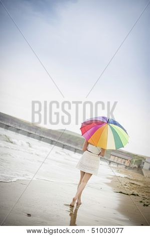 Woman Walking Along The Beach With An Umbrella