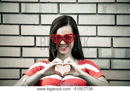 Beautiful young brunette with heart-shape eyeglasses make heart with fingers, with brick wall in the background