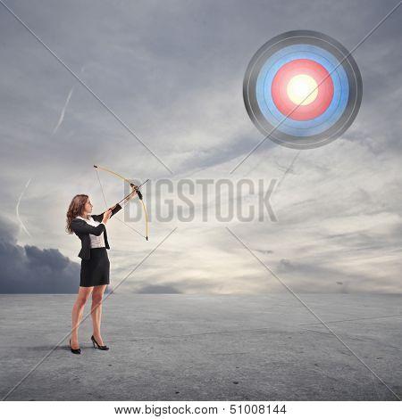 beautiful career woman pulls arrow with bow