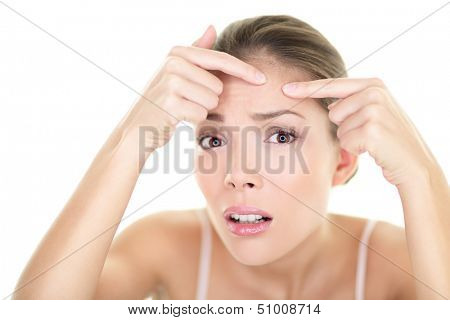 Acne spot pimple spot skincare beauty care girl pressing on skin problem face. Woman with skin blemish looking at mirror isolated, white background. Beautiful young Asian Caucasian female model.