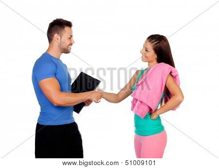 Handsome personal trainer with a attractive girl isolated on a white background