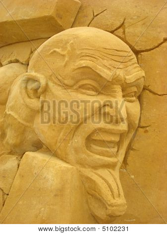 Face Of Man With A Wicked Grimace From Sand