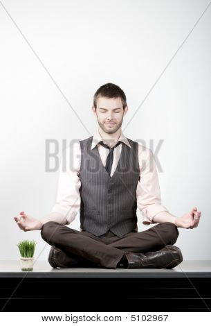 Handsome Young Businessman Meditating On Desk