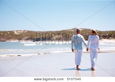 Stock photo : Couple Holding Hands While Walking By The Beach