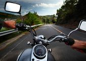 foto of biker  - Rider driving motorcycle on a rural road in a mountains - JPG