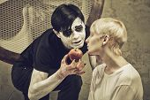 stock photo of lunate  - Crazy guy with apple and sad girl in a cell of an lunatic asylum - JPG