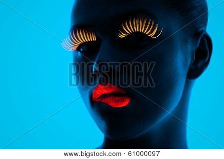 close-up portrait of young woman wearing UV lashes and lipstick under blacklight