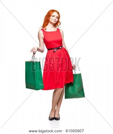 young adult readhead in red dress holding green shopping bags, isolated on white, studio shot