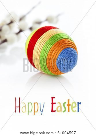Colorful easter egg on white background. Catkins in background. Space for text