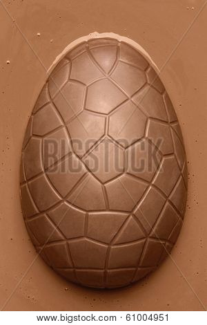 Chocolate Easter egg emerging from smooth melted milk chocolate