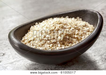 Quinoa flakes in small black bowl over rustic wood.