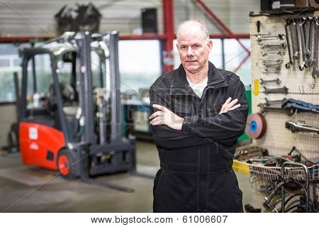 middle aged mechanic standing in a forklift garage in his uniform with a forklift and his repair tools in the background