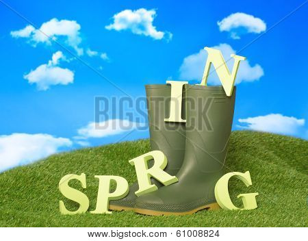 Spring concept with wellington boots and painted wooden letters