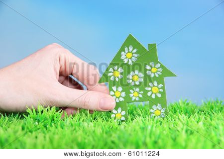 Little paper house in hand  on green grass on blue sky background