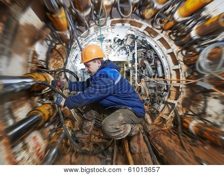 Tunneller sinker worker connecting equipment in tunnel of sewe? collector at undergroung working