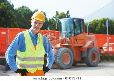 construction worker in safety protective work wear at construction site in front of loader machinery