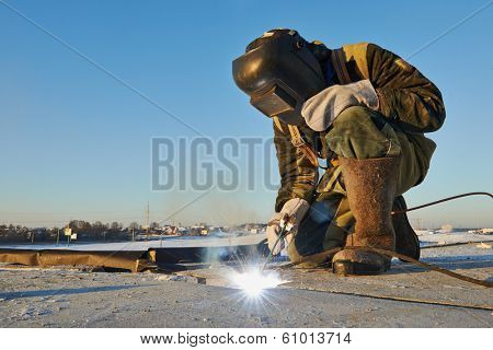 welder working with electrode at arc werding in construction site winter outdoors