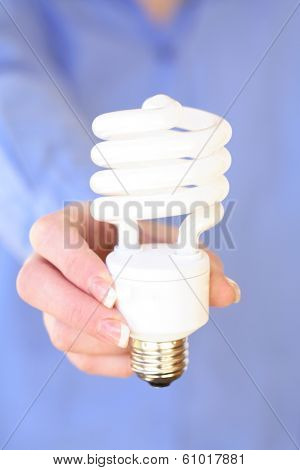 Woman wearing blue shirt holding compact fluorescent light bulb