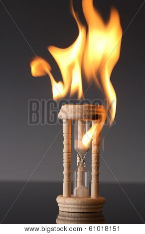 Hour glass on fire with grey background